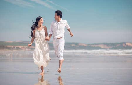 Vietnamese couple in love running on beach