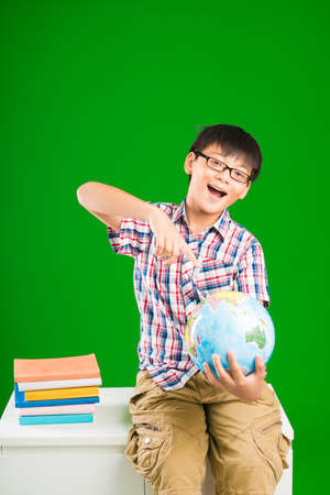 Cheerful schoolboy pointing at the globe in his hands