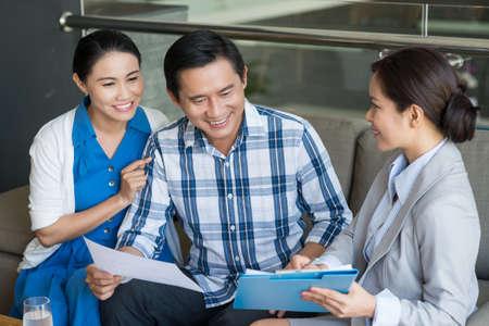 ベトナム人カップルと契約を議論するセールスレディ