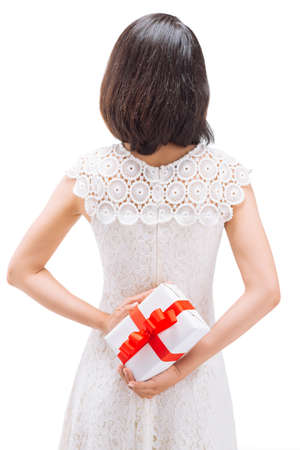 Girl hiding gift behind her back, rear view Stock Photo