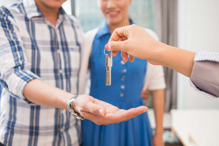 accommodation broker: Hands of estate agent giving keys to the couple Stock Photo