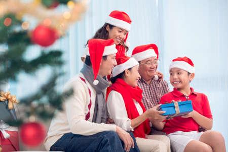 幸せなベトナム家族のクリスマスを交換するため一緒に集められたプレゼントします。