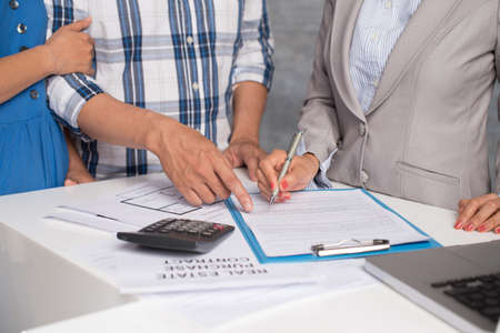 accommodation broker: Cropped image of couple and estate agent signing a contract