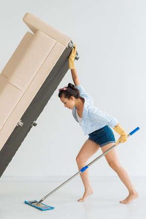 estereotipo: Sofá de levantamiento de ama de casa para limpiar debajo del piso Foto de archivo