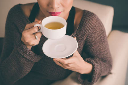 Unrecognizable woman holding a hot cup of tea and blowing on it