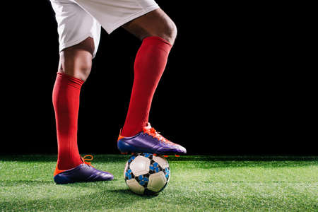 Soccer player standing with his foot on the ball, sideview Stock Photo