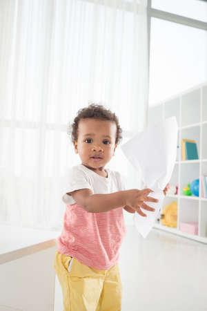 Cute little boy crumpling paper