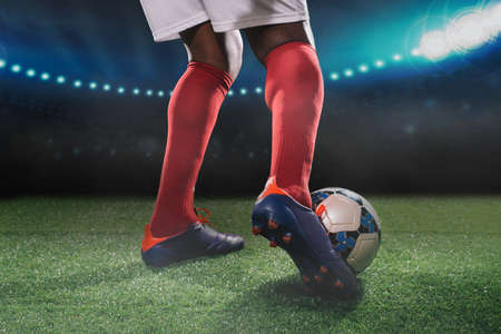 Legs of soccer player kicking off the ball