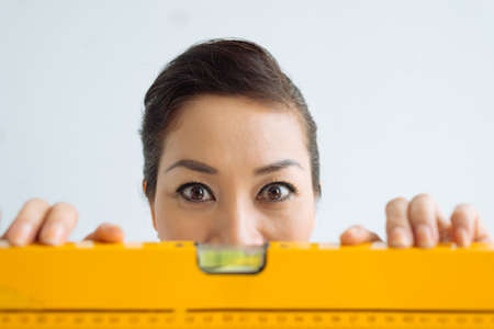 Woman with a spirit level staring wide-eyed at the camera