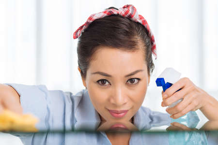 Close-up of beautiful girl cleaning table with a spray