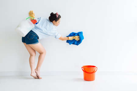 microfiber: Housewife in denim shorts cleaning the wall Stock Photo