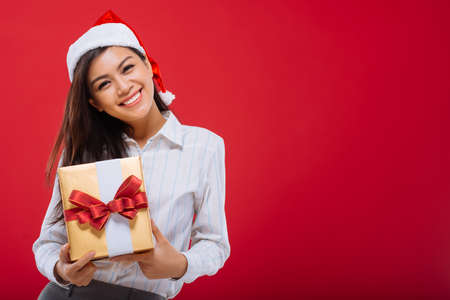 Attractive Asian girl with Christmas present in her hands, isolated on red