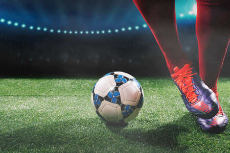 Close-up of soccer ball and feet of soccer player Stock Photo