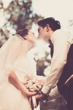 tenderly: Newlywed couple tenderly kissing outdoors