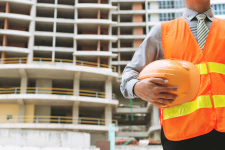 Cropped image of engineer with a hardhat at the construction site