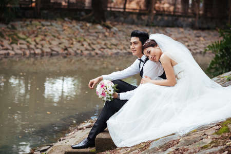 Newly married Vietnamese couple sitting on the bank of the river Stock Photo