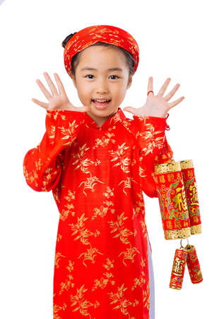 Portrait of Vietnamese girl in traditional clothing holding firecrackers