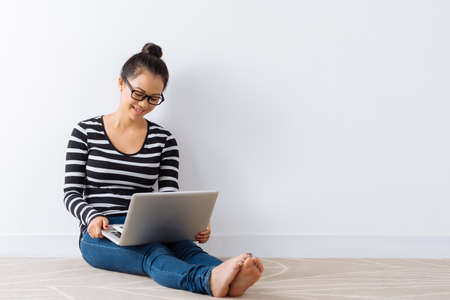 Young girl sitting on the floor and watching something on the laptop