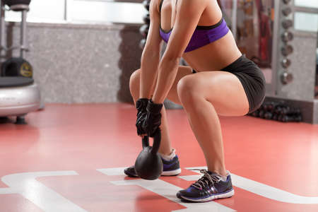 Cropped image of professional sportswoman doing kettlebell weight exercise