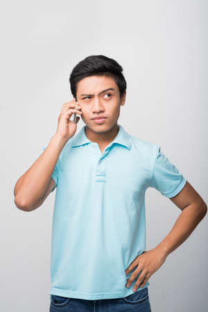 Portrait of suspicious young man talking on the phone Stock Photo