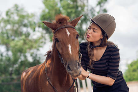 Young girl in jockey cap kissing her horse Stock Photo