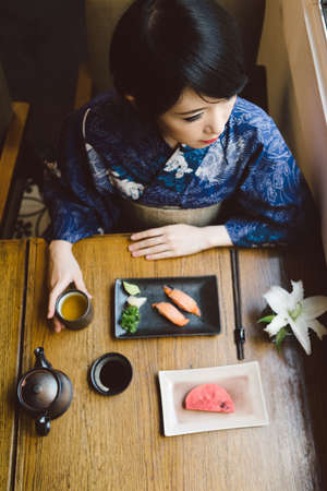 japanese food: Young woman in yukata eating traditional Japanese food, view from above