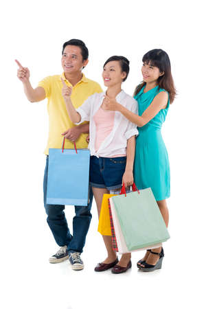 Smiling Vietnamese family with shopping bags pointing aside Stock Photo
