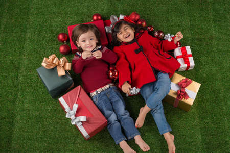 Happy little boy and girl lying on the floor surrounded by Christmas presents