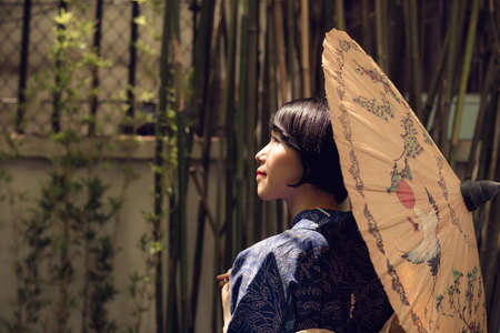 Japanese woman in yukata with traditional umbrella