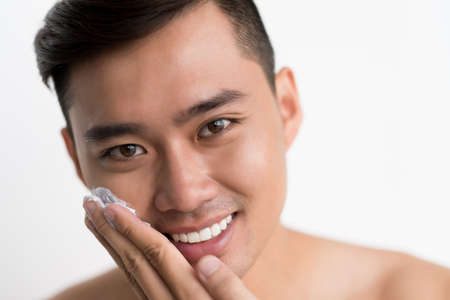 Face of Asian young man applying shaving cream