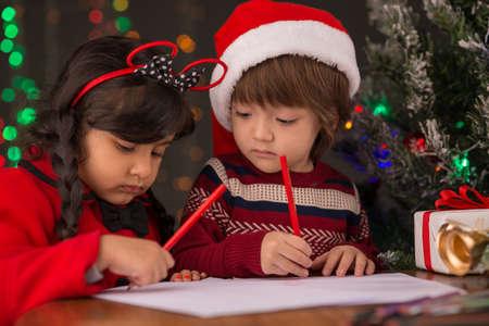 Deux petits enfants écrivant des lettres pour le Père Noël Banque d'images