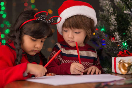 Two little children writing letters for Santa Claus