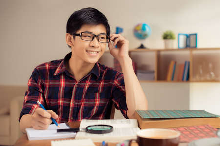 Smiling student in glasses making notes in his copybook