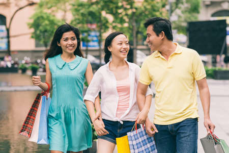 Teenage girl and her parents walking along the street after shopping Stock Photo - 73115776