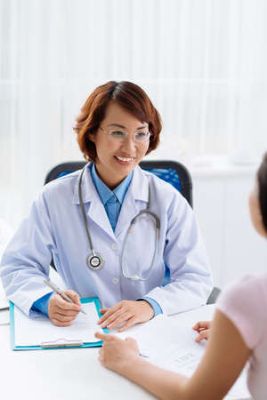 Smiling doctor filling medical report for her patient Stock Photo