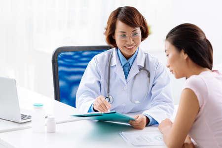 女性の医師が若い女性に医療検査を説明します。 写真素材