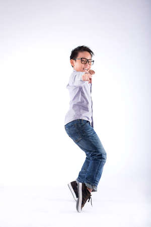 Smiling Vietnamese boy standing on tiptoes and pointing at you Stock Photo