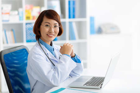 Vietnamese physician working on laptop in her office Stock Photo