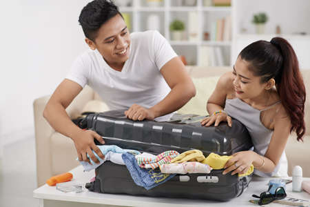 Couple trying to close overstuffed suitcase