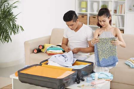 休暇のためのアジアの若いカップル梱包スーツケース 写真素材