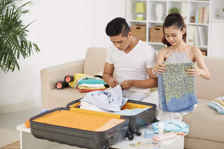 Asian young couple packing suitcase for vacation