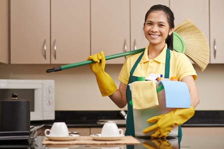 Portrait of lovely Vietnamese girl with bucket of cleaning supplies and a broom