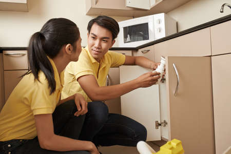sink drain: Young Vietnamese plumber and his female assistant installing sink in the kitchen Stock Photo
