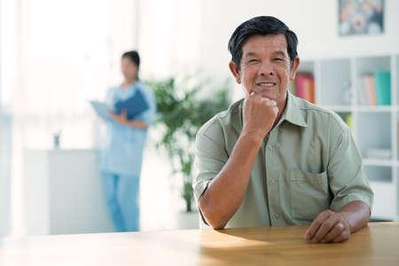 doctors smiling: Portrait of smiling senior man in doctors office