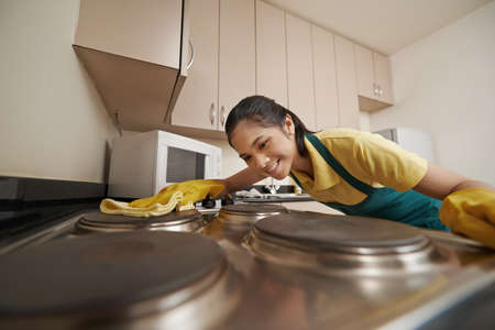Woman in rubber gloves cleaning electric stove