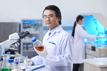 pharmacologist: Asian pharmaceutical chemist with a bottle with medical liquid