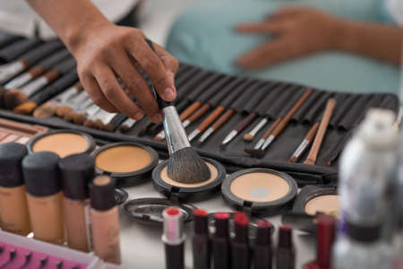 visage: Make-up artist using natural animal hair brush to apply pressed powder Stock Photo