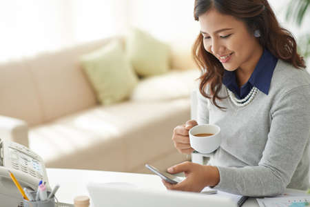 Smiling business woman drinking coffee and reading message on her phone Stock Photo