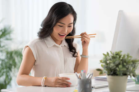 Chinese business woman with chopsticks having noodle soup for lunch