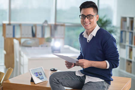 Smiling Vietnamese man with a document sitting on table